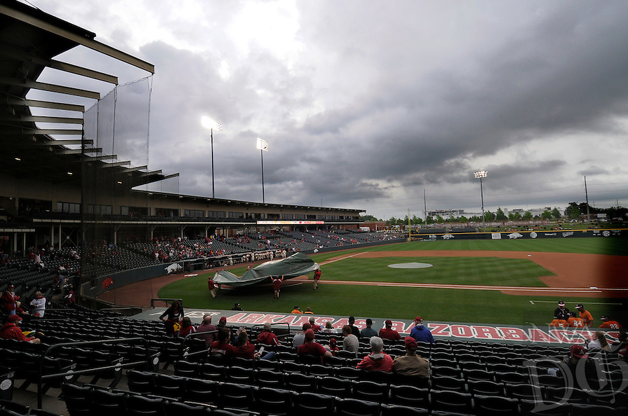 NWA Democrat-Gazette/J.T. WAMPLER -- The Baum Stadium grounds crew covers home plate before a rain delay Sunday May 10, 2015. The Hogs played one of two scheduled games against Tennessee and won 5-2.