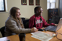 NWA Democrat-Gazette/CHARLIE KAIJO Bentonville High School student Imana Junior, 15 (from right), works on an essay with her mentor Ashley Skaggs, Monday, February 12, 2018 at the Boys and Girls Club in Bentonville. <br /><br />Junior won a $5,000 academic scholarship as the Boys and Girls Club Youth of the Year winner for Benton County. <br /><br />Junior who has been a member of the club for 10 years competed with six other youth in an essay contest. Each competitor had to write three essays on their experience at the club, their personal brand and their vision for America&acirc;&euro;&trade;s youth.<br /><br />Junior will compose a speech from her essays that she'll share on March 8 at the Youth of the Year banquet  at the John Q. Hammons Center and at the state level competition in Little Rock from March 12-14 where she will have an opportunity to win another $5,000 academic scholarship. <br /><br />&quot;The mission of the Boys and Girls Club is to empower young people to reach their full potential as productive caring citizens,&quot; said Sarah Heimer, chief executive officer. &quot;Youth of the Year allows them to be part of something bigger than their local community. It allows them to participate with other youth across America.&quot;<br /><br />One of the topics Junior wanted to share was about her experience being bullied. <br /><br />&quot;With bullying, I feel like there needs to be a support system and I have that,&quot; said Junior. &quot;My bond with my mom is really special to me. She was my support system when I was getting bullied and she was the one who made it stop. There are no words for how much I love my mom.&quot;