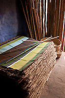 A pile of woven rush mats is stored in a corner of the room
