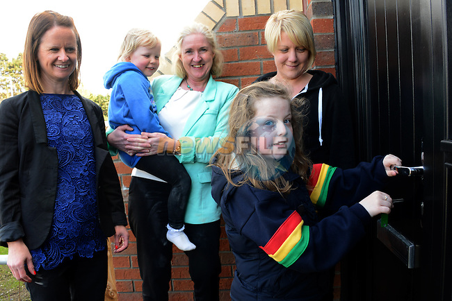 Ten year old Lucy Clinton opens the door of her family's new home looking on are her Mother Donna Cunningham, sister Abbey Clinton and Sorcha Malone and Jackie Knight who are housing officers with North East Housing.