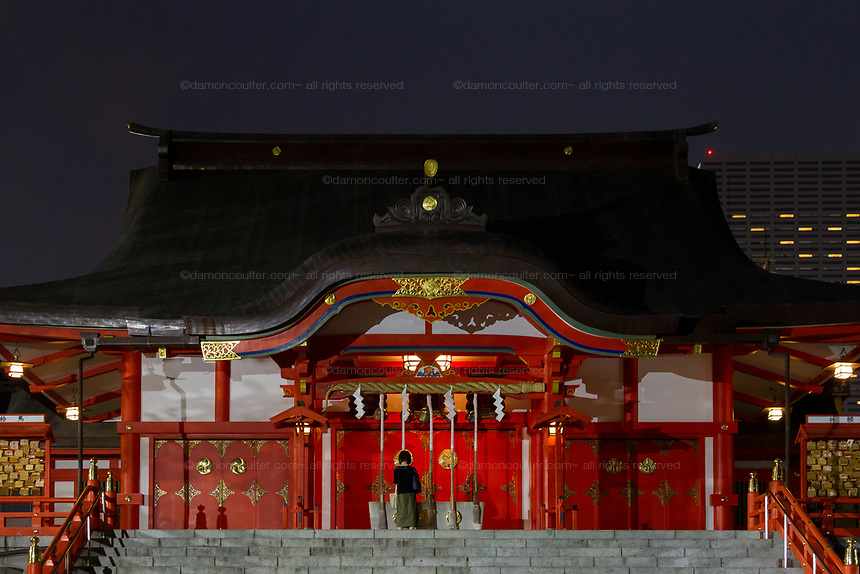 A woman prays at Hanazono Shrine at night in Shinjuku, Tokyo, Japan. Saturday August 24th 2019