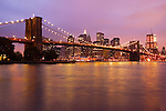 A fine art capture of the Brooklyn Bridge at Night with NYC skyline in the background.