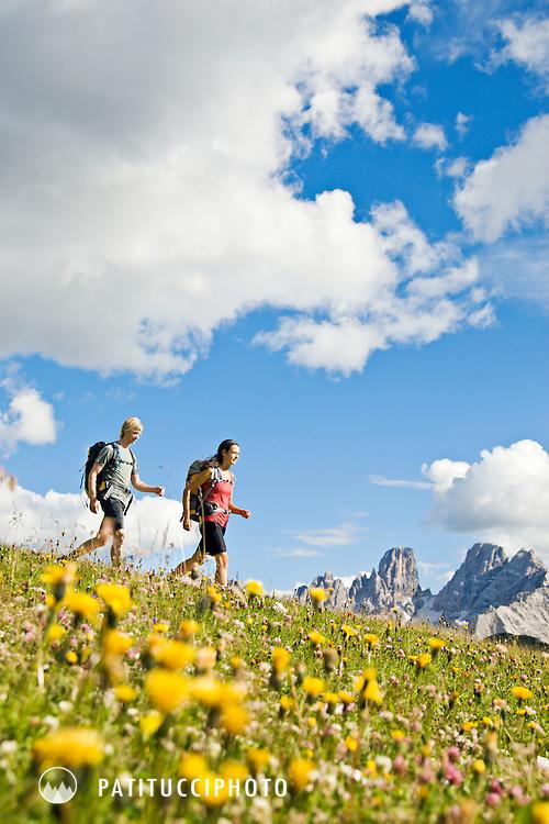 Norbert Notdurfter and Patrizia Taibon hiking through spring wild flowers in the Italian Dolomites
