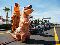 Oct 27, 2018; Las Vegas, NV, USA; Cameron McMillen (center), son of NHRA top fuel driver Terry McMillen wears a dinosaur Halloween costume during qualifying for the Toyota Nationals at The Strip at Las Vegas Motor Speedway. Mandatory Credit: Mark J. Rebilas-USA TODAY Sports