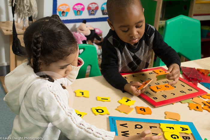 Education Preschool 3-4 year olds boy and girl working on wooden alpahbet puzzles