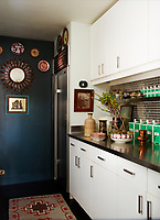 The compact kitchen is painted in Farrow & Ball's Carriage Green. The fitted cabinets are by Ikea, the refrigerator is by Sub-Zero, the Navajo rug is from Kandi's.