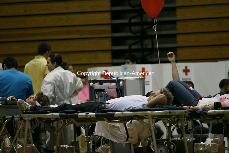 """TORRINGTON, CT - 5 February, 2009 - 020509MO02 - Senior Robert Schapp, 17, center, was among nearly 100 Red Raiders who signed up to donate blood Thursday at Torrington High School. Schapp said he chose to donate to help people, and because """"I don't need it all,"""" adding that the free balloon is a nice perk. Red Cross officials said the school is among the more giving  in the state when it comes to blood drives, which are scheduled here three times a year. Each pint of donated blood can help up to three people. Call 800-GIVE LIFE for details on upcoming blood drives in the area. Jim Moore Republican-American."""