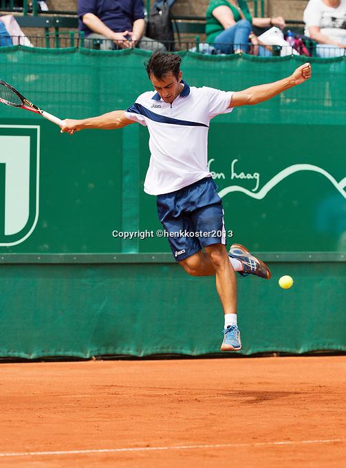 10-07-13, Netherlands, Scheveningen,  Mets, Tennis, Sport1 Open, day three, Lorenzo Giustino (ITA) jumps over the ball<br /> <br /> <br /> Photo: Henk Koster