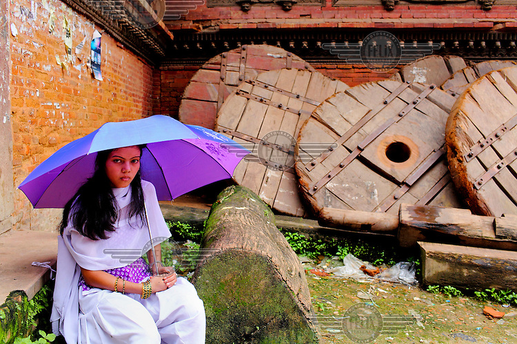 A woman sits under an umbrella selling religious books on the street.