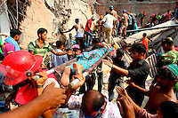 A woman is pulled from the rubble of the Rana Plaza complex in Savar by rescuers and civilian helpers. The 8 storey building, which housed a number of garment factories employing over 3,000 workers, collapsed on 24 April 2013. By 29 April, at least 380 were known to have died while hundreds remained missing. Workers who were worried about going to work in the building when they noticed cracks in the walls were told not to worry by the building's owner, Mohammed Sohel Rana, who is a member of the ruling Awami League's youth front. He fled his home and tried to escape to neighbouring India after the building collapsed but was caught by police and brought back to Dhaka. Some of the factories working in the Rana Plaza building produce cheap clothes for various European retailers including Primark in the UK and Mango, a Spanish label. . /Felix Features