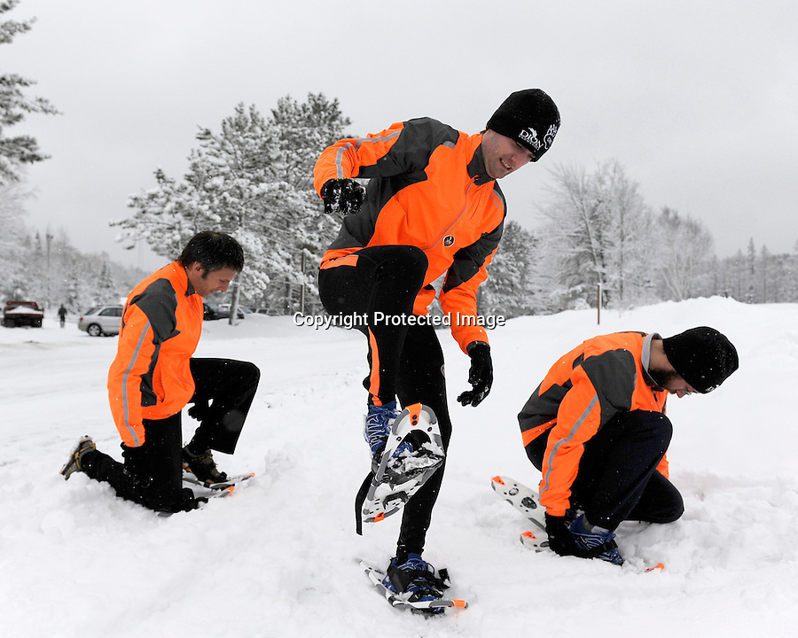 Members of the Dion snowshoe team strap on their shoes in preparation of the Dion Snowshoe USSSA National Snowshoe Championship at Cable, WI, on March 12, 2011.