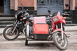 Havana, Cuba; two old motorcycles, with sidecars, parked in front of the Bacardi Building, the former headquarters of the Bacardi Rum empire