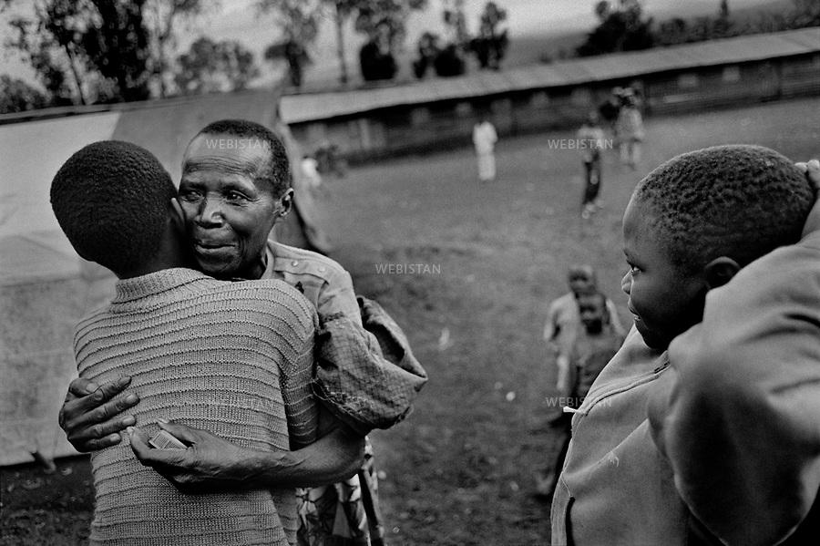 1995. Zaire. Democratic Republic of the Congo (DRC). Sud-Kivu Province. Camp of Mudaka. Simon, a Rwandan Hutu refugee boy who fled his country during the 1994 Rwandan Genocide and who had lost his family, clasps his grandmother Seraphine in his arms. She has just been found again after a year of separation and research. Zaïre. République Démocratique du Congo (RDC). Province du Sud-Kivu. Camp de Mudaka. Simon, un garçon réfugié rwandais hutu qui a fui son pays pendant le génocide au Rwanda en 1994, et qui avait perdu sa famille, serre sa grand-mère Séraphine dans ses bras. Elle vient juste d'être retrouvée après un an de séparation et de recherche.