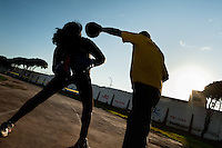 A Peruvian woman practices sparring with her coach in the outdoor boxing school at the Telmo Carbajo stadium in Callao, Peru, 4 April 2013.