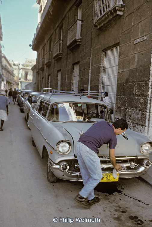 A taxi driver cleans his car in Central Havana.  High cost and the US economic blockade have meant that very old American-made cars are patched up and kept on the road to compensate for lack of imports.