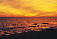 Scenic seascape of sunrise over a beach and ocean waves.