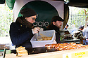 London, UK. 25.10.2014. A woman cooking veggie burgers on a food stall at Borough Market, Southwark. Photograph © Jane Hobson.