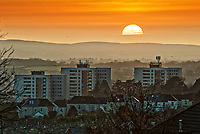 The sun sets over blocks of flats in the Sketty area of Swansea in south Wales, UK. Friday 15 February 2019