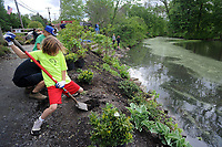 Lukas Ricciardi, of Yardley, Pennsylvania digs a hole to plant a shrub during a community cleanup of Lake Afton to provide some relief for the algae-plagued and mucky man made lake Saturday, May 6, 2017 at Lake Afton in Yardley, Pennsylvania. (WILLIAM THOMAS CAIN / For The Philadelphia Inquirer)