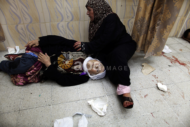 Palestinian woman, wounded in an Israeli strike on a compound housing a U.N. school in Beit Hanoun, in the northern Gaza Strip, lay on the floor of an emergency room at the Kamal Adwan hospital in Beit Lahiya, Thursday, July 24, 2014. Israeli tank shells hit the compound, killing more than a dozen people and wounding dozens more who were seeking shelter from fierce clashes on the streets outside. Gaza health official Ashraf al-Kidra says the dead and injured in the school compound were among hundreds of people seeking shelter from heavy fighting in the area.. Photo by Ali Jadallah