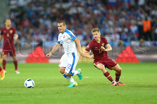 15.06.2016. Lille, France. UEFA Euro 2016 Group B soccer match Russia and Slovakia at Stade Pierre Mauroy in Lille Metropole, France, 15 June 2016.  Viktor Pecovsky (slo)turns Oleg Shatov (rus)