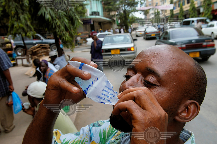 Man drinking water sold in plastic bags downtown - the tap water is undrinkable.