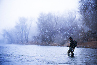 An angler wades into the Big Hole River in western Montana during a snow squall.