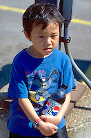 Boy age 4 walking at Cinco De Mayo Festival.  St Paul  Minnesota USA