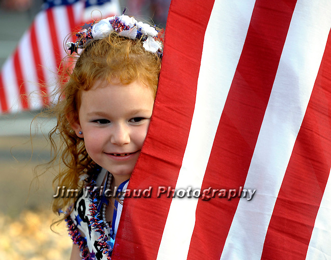 Megan Carcia, 6, of Ellington, peaks from around an American flag sitting in her wagon waiting for the parade to start,  during the annual July in the Sky Push, Pedal, Pull Patriotic Parade, in downtown Rockville, Tuesday, July 1, 2014, in Vernon.  (Jim Michaud / Journal Inquirer)