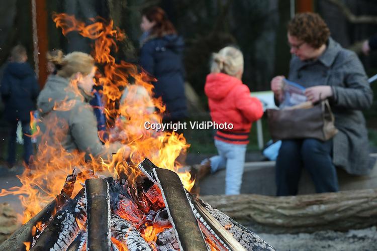 Foto: VidiPhoto<br /> <br /> RHENEN - Bezoekers van Ouwehands Dierenpark in Rhenen warmen zich dinsdag aan een kampvuur bij de ingang. De Nederlandse dierenparken beleven op dit moment toptijden. Door het zachte weer in combinatie met de Kerstvakantie staan er vanaf 's morgens vroeg al enorme rijen voor de kassa's. Het is in geen jaren gebeurd dat zoveel dagjemensen tijdens de Kerstvakantie naar de pret- en dierenparken kwamen.