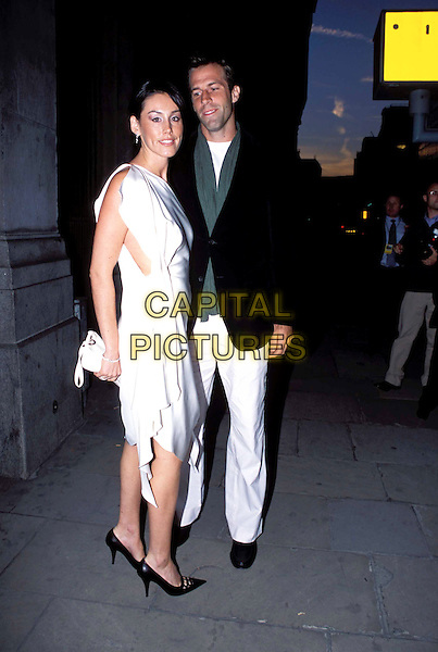 GREG RUSEDSKI & WIFE.Lycra British Style Awards 2003, Old Billingsgate Market, EC3.white dress, flowing, sleeveless, white trousers, black suit jacket jacket, look-alike, full length, full-length.www.capitalpictures.com.sales@capitalpictures.com.© Capital Pictures