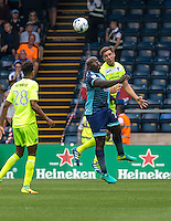 Luke Prosser of Colchester United heads clears from Adebayo Akinfenwa of Wycombe Wanderers during the Sky Bet League 2 match between Wycombe Wanderers and Colchester United at Adams Park, High Wycombe, England on 27 August 2016. Photo by Liam McAvoy.