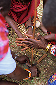 Lolgorian, Kenya. Siria Maasai moran (young warriors) making fire using traditional wood friction method.