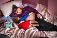 "A woman  8 months pregnant breastfeeds her little girl aged 3 years old while they both lie on the family bed.<br /> <br /> Image from the ""We Do It In Public"" documentary photography project collection: <br />  www.breastfeedinginpublic.co.uk<br /> <br /> Dorset, England, UK<br /> 14/02/2013"