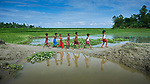 Children walk along an eroded path in Kunderpara, a village on an island in the Brahmaputra River in northern Bangladesh. Severe flooding in August 2017 eroded village farms and damaged houses.