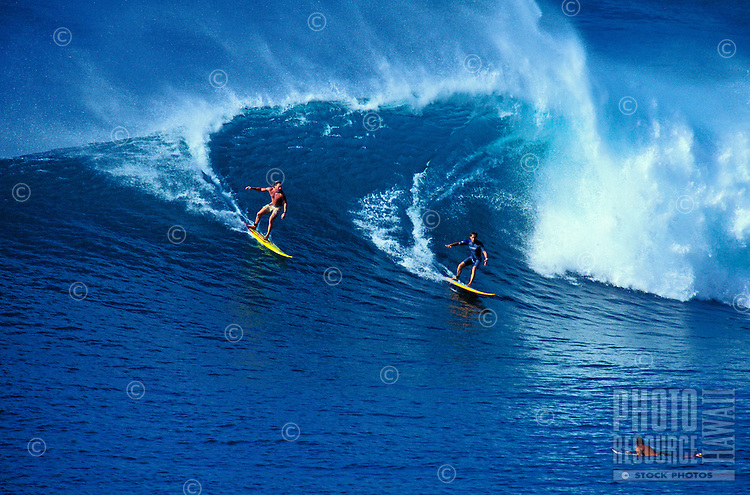 Two surfers riding a wave and one surfer paddling at Honolua Bay on Maui