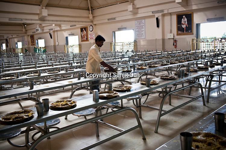 A volunteer is seen clearning the empty leaf plates at the Sai Prasadalaya that feeds an approximate number of 30000 Sai Baba devotees as a Prasad (holy meal) every day. Free Prasad meals are served to all the devotees. An approximate number of 1000 devotees are served everyday with this facility. Expenses for a plate of Prasad meal  is around Rs. 15/- but the Saibaba Sansthan provides prasad meals to all Sai devotees to Rs. 6/- only. The prasadalaya at the Shirdi Sai Baba Shrine is powered by a large array of concave mirrors that transform sunlight to energy to create hot water and steam for the cooking process. Photograph: Sanjit Das