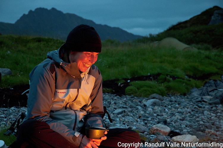 Dame slapper av med kopp i hånden foran bål. ---- Woman relaxing in front of camp fire.