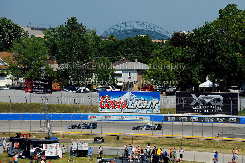 Rubens Barrichello (#8) and Tony Kanaan (#11) race through turn 2 with Milwaukee's Miller field in the background.