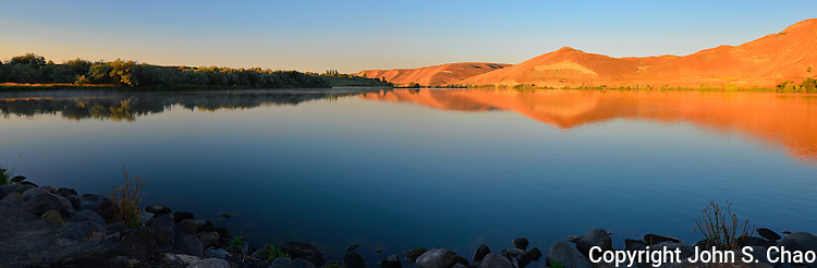 Panorama of sunrise highlighting Hagerman Fossil Beds National Monument, reflecting, looking south on Snake River, Idaho.