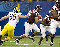 Logan Thomas of Virginia Tech runs the ball away from Craig Roh of Michigan during Sugar Bowl game at Mercedes-Benz SuperDome in New Orleans, Louisiana on January 3rd, 2012.  Michigan defeated Virginia Tech, 23-20 in first overtime.