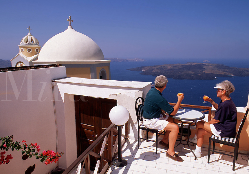 A senior couple enjoys a meal on a balcony overlooking the Mediterranean Sea. Santorini, Greece.