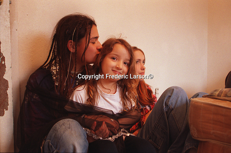 Jazman Herandez in her bedroom in Sacamento kisses her younger sister Jenee, age 4, why she is under house arrest.
