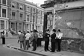 Police and local residents wait for the carnival procession on the corner of Basing Street and Westbourne Park Road, Notting Hill, 1981.