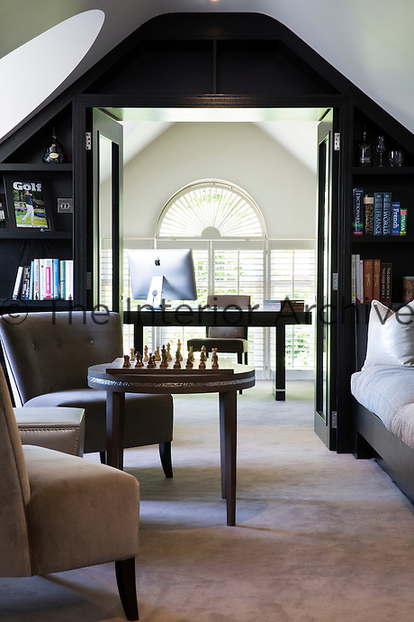 The sloping library ceilings are emphasised by the use of quarter cut darkly stained oak joinery which encompass built-in shelving. A set of double doors lead through to the study area beyond.