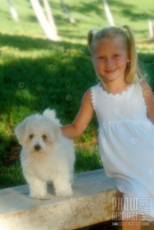 Young girl with small bichon frise puppy