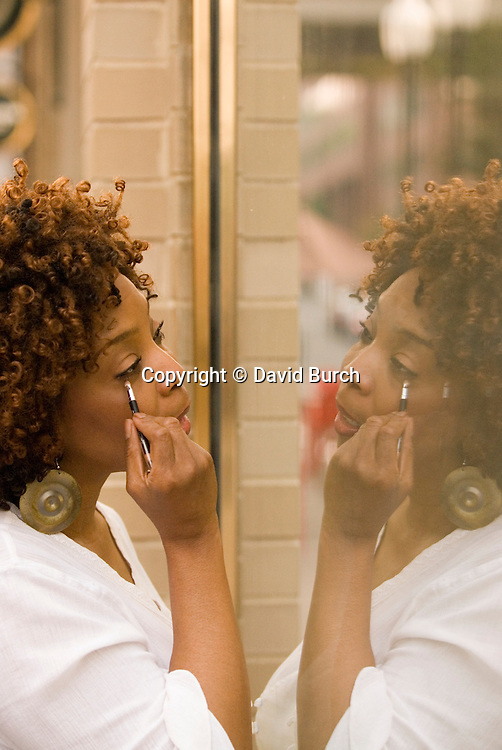 African American woman looking at her reflection, applying eyeliner
