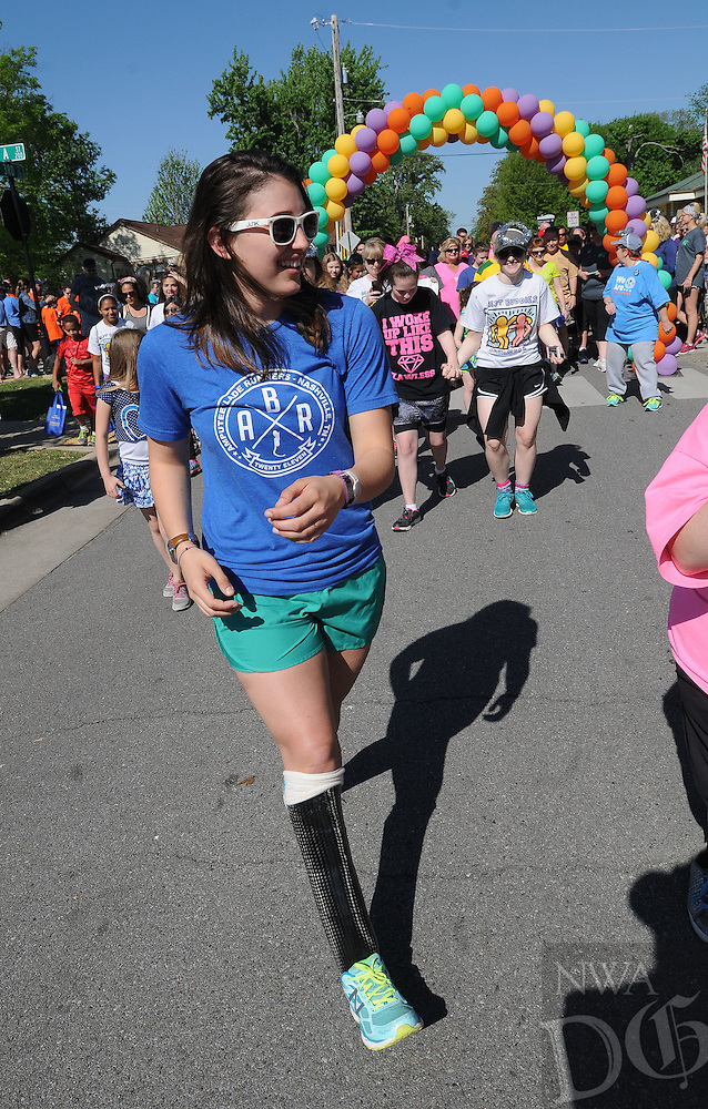 NWA Democrat-Gazette/FLIP PUTTHOFF <br /> BUDDIES WALK TOGETHER<br /> Molly Rhodes, who has a prosthetic leg, leads the start Saturday April 23, 2016 of the Best Buddies Friendship Walk at Lawrence Plaza in downtown Bentonville. The one-mile walk raised funds for the Best Buddies program to aid children with physical or mental disablilities. Rhodes had a leg amputated in 2014 but now swims, runs and completes in triathlons. Best Buddies also matches up special needs kids with similar interests to foster friendship, said Kathy Breed, an organizer of the walk. Best Buddies is based in Little Rock, but a goal of the group is to establish an office in Northwest Arkansas, she said.