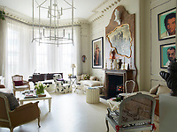 In the sitting room, a faux marble panel surrounds a real marble fireplace and an engraving of a Piranesi-style ruin is outlined in an irregular gilded frame whose shape echoes a Cocteau drawing. Resin falcons are painted white to mimic porcelain and a pair of Warholesque portraits by the artist Skid Stewart hang over a daybed. The eclectic style is offset by calm: white walls, white wood floors, relatively spare arrangements of traditional furniture and neutral upholstery.