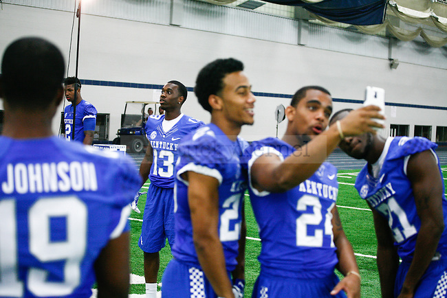 "Wide receiver Jeff Badet poses for a picture in the background while some players take a ""selfie"" during UK football media day at Nutter Field House in Lexington, Ky., on Friday, August 8, 2014. Photo by Adam Pennavaria 